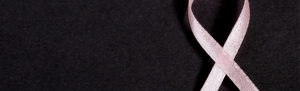 Pink ribbon on black background.